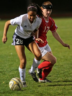 Cathedral City's Miyah Coleman (29, white jersey) defends the ball from Palm Desert's Afton Kalkoske (17, red jersey) during a girls' soccer game on Tuesday, January 6, 2015 at Cathedral City High School.