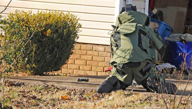 A member of the Montgomery County Sheriff's Office Bomb Squad works with a pipe bomb found at a house on Heather Drive on Tuesday.