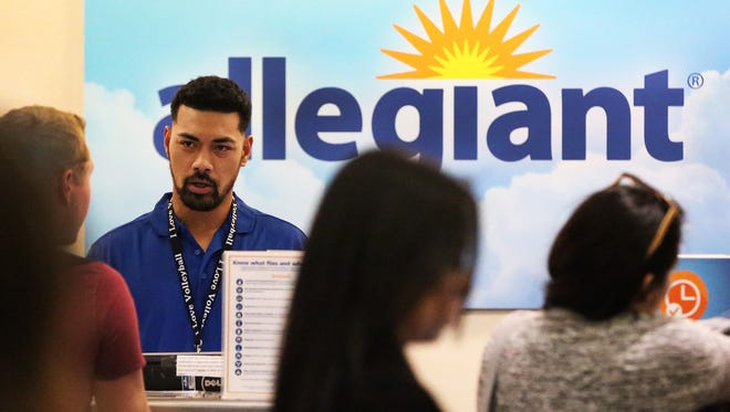 Allegiant customer service representative Leifitele Mamea, left, assists travelers on route to Las Vegas at the El Paso airport Friday.