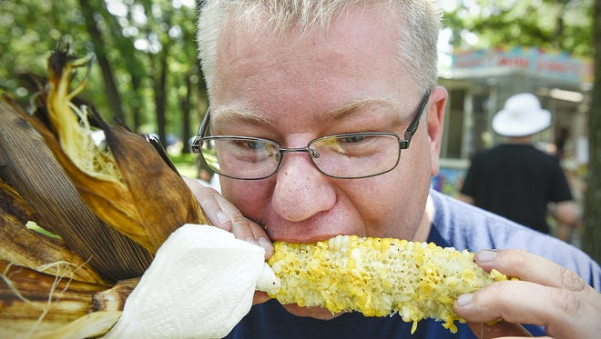 Dan Fletcher, Sartell, followed up a pork chop with an ear of sweet corn during the 2016 Rapids River Food Fest in the Municipal Park in Sauk Rapids.