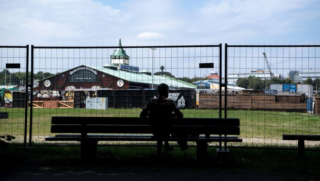 A man sits in front of a fence on the Oktoberfest grounds in Munich, Germany, on August 17, 2016. In the background is the construction site for the beer festival.