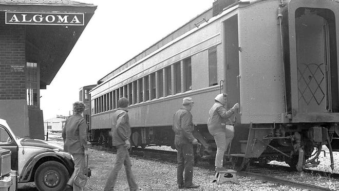 Harold Heidmann shot this photo in 1976 as passengers were boarding an excursion train at the Algoma depot, bound for Casco. Passengers that day were looking for a unique experience on the Ahnapee & Western tracks.  One experience they did not have that day was drinking from public-use cups. By early fall of 1910, the State of Wisconsin mandated the end of public cups on trains, and passengers who didn't bring their own cups were compelled to buy one if they wanted a drink. Patrons were not happy so, as an accommodation, informative placards were hung above drinking places in trains and stations. Strange as it would have seemed to the 1976 passengers, public cups were preferred in 1910.  Heidmann's photos are found at Algoma Public Library.