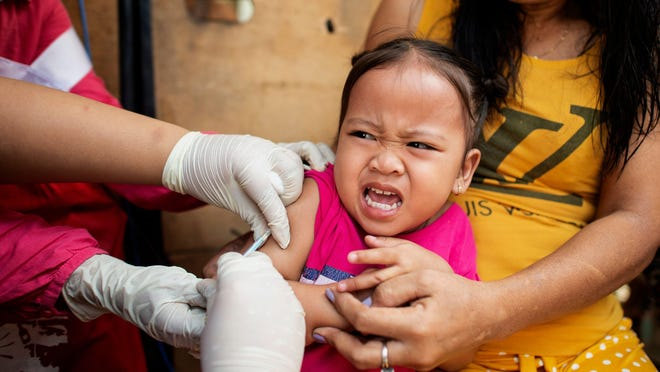 A child reacts during a Philippine Read Cross Measles Outbreak Vaccination Response in Baseco compound, a slum area in Manila on Feb. 16, 2019.