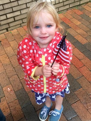 Brylee Hupman, 3, braved the elements on Saturday to watch the Veteran's Day Parade.