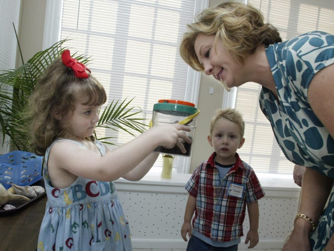 Pre-K student Lizzie Bagby, left, shows her frog to
