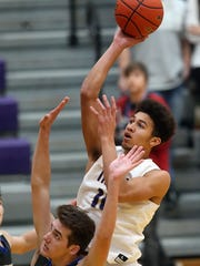 North Kitsap's Kai Warren goes up for a shot over Olympic's Keaton Dean during the third quarter of their game in Poulsbo on Tuesday, December 12, 2017.