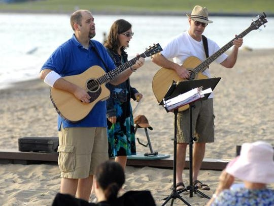 The Rev. Jason Pittman, left, sings a song of worship,