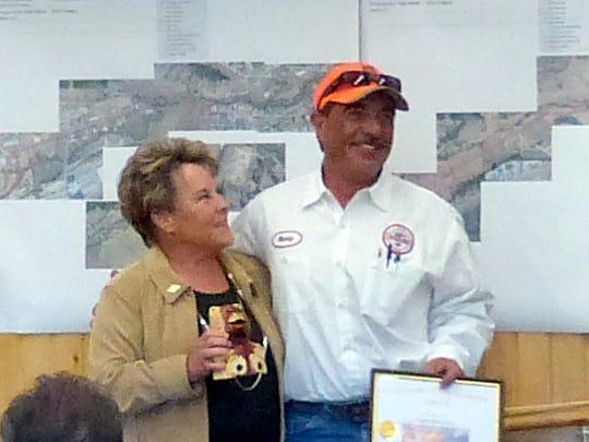 Debi Lee hands Marty Luna a plaque and carved bear