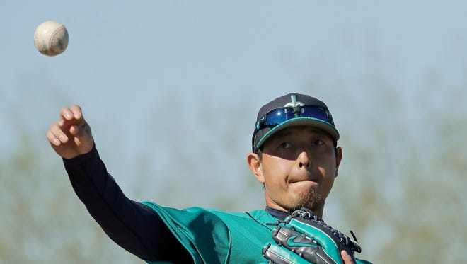 Mariners pitcher Hisashi Iwakuma throws during the first workout of the spring Wednesday in Peoria, Ariz.