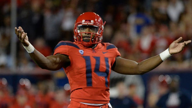 Arizona Wildcats quarterback Khalil Tate (14) signals to the crowd during the first half against the Washington State Cougars at Arizona Stadium.