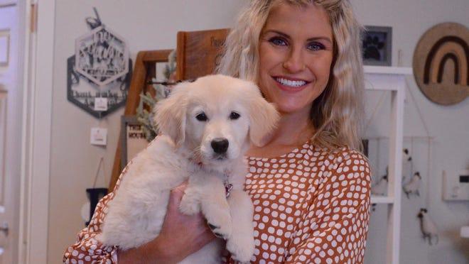 Heather TenHarmsel holds her three-month-old golden retriever, Poppy, in her retail store The Poppy Peach.