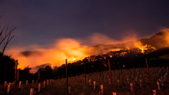 Fire glows on a hillside in Napa, California on October 9, 2017