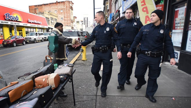 Three Paterson Police Officers, (L to R) Edward J. Akins, Salvador Brancato and Ferdi Abedinoski who graduated from Police Academy last week, greet a vendor Dean Rogers, during their patrols for the first time in commercial shopping districts in downtown Paterson on 12/19/17.