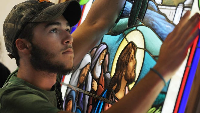 Apprentice Joseph Llano holds a stained glass panel of Jesus at Gethsemane in place while it is secured.