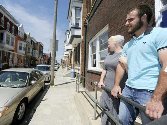 Tyler Burkholder, who works at Tidings of Peace Mennonite Church, looks over the 300 block of East Poplar Street in York with his wife, Sarah. The church runs a school of about 40 students from K-12. Tyler Burkholder, 21, said outreach programs commonly involve large groups of city kids. 'I have a heart for the kids,' he said. 'I made bad choices as a kid, and I'd like to see them do better than I did and better than some are doing now.'