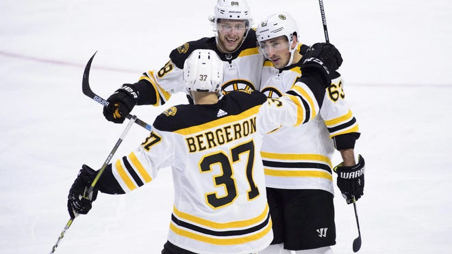 """Bruins winger Brad Marchand, right, is hoping there will be plenty of moments like this -- celebrating a goal with line mates Patrice Bergeron and David Pastrnak -- during the upcoming resumption of the season, but Pastrnak is still under the """"unfit to participate"""" designation."""