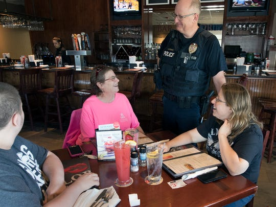 From the left seated, Christopher Glassmyer, Jan Frey and Jess Glassmyer listen to York City Police Officer Greg Schick during the Cops and Lobsters fundraiser for the York County Special Olympics at Red Lobster in Springettsbury Township.