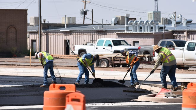Mesa Verde construction crews work to spread asphalt on South Florida Avenue on Friday morning.