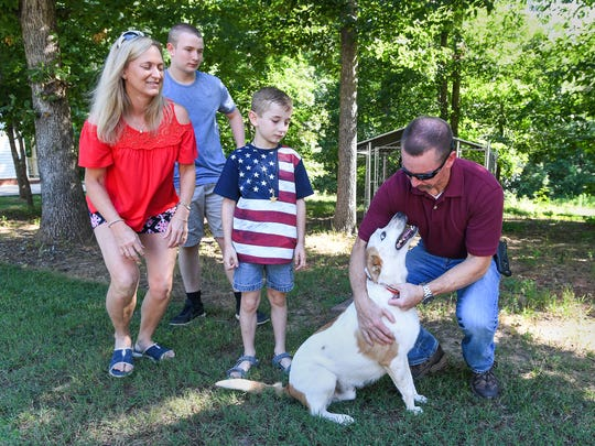 Greenville County Sheriff's Office Chief Deputy John Eldridge plays with the family dog Isaac with his family, from left, wife Amy, and sons C.J. and Eli at their home in Travelers Rest on Wednesday, June 28, 2017. Eldridge will be retiring Friday after 27 years on the force.