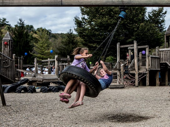 Savannah Woody and Maygen play on the tire swing at