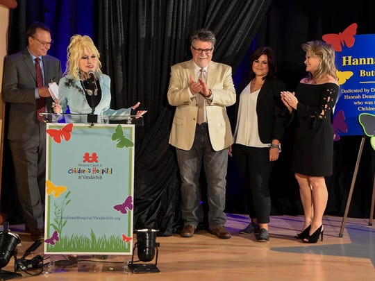 President and CEO of Vanderbilt Medical Center, left, Dolly Parton, Richard Dennison, Hannah Dennison and Dolly's sister Rachel George join the stage at the dedication of the Hannah Dennison Butterfly Garden at the Monroe Carell Jr. Children's Hospital  in Nashville, Tenn., Thursday, May 17, 2018.