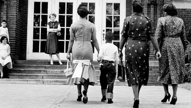 Erroll Groves, second from left, with his mother, Mrs. Iridella Groves, left, and other family members walk up to the doors of Buena Vista School on the first day of school Sept. 9, 1957.