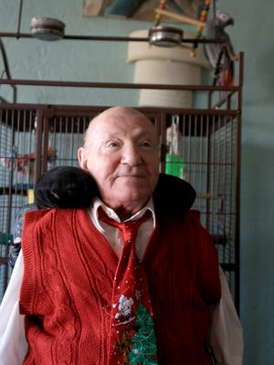 Johannes Michalski, pictured here with his parrot, Jacko, became a painter after his arms were amputated when he was only 10 years old.