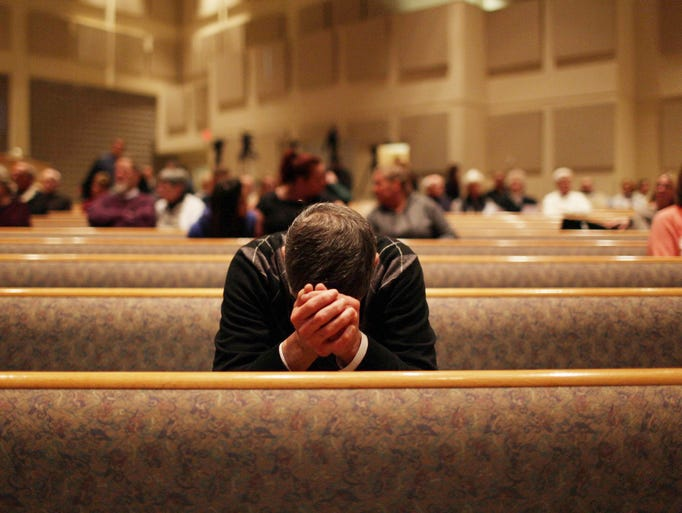 A member of the community prays before the start of