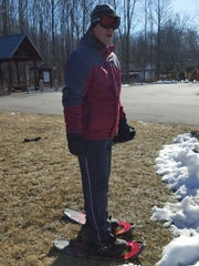 Poughkeepsie resident Ricky Miller prepares for the Special Olympics New York Winter Games by snowshoeing on grass in Hyde Park.