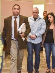 Guam Police Officer Mark Torre Jr., center, walks out