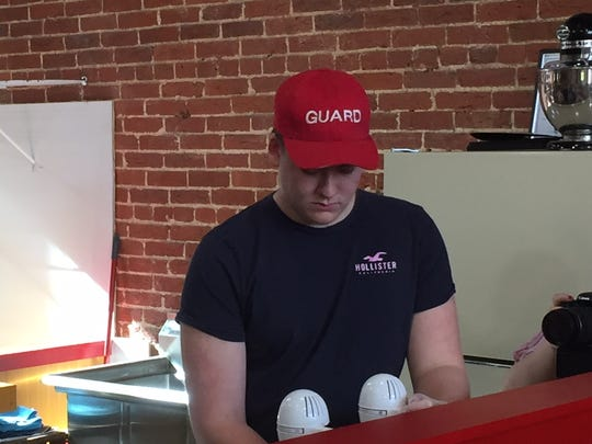 17-year-old Gavin Binner quickly learning running a business will take hard work, making a milkshake for a customer at the grand opening of Dough & Shake.