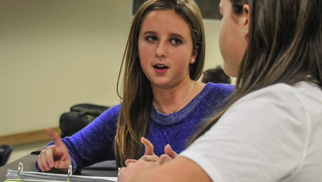 Morgan Wood, left, helps a student with schoolwork last year during a mentoring program.