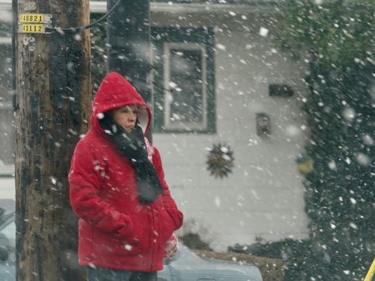 A woman waits for a bus in the snow on Kirkwood highway and Elsmere Tuesday morning.