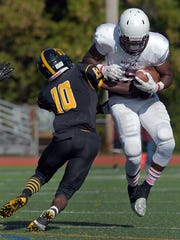 Aquinas' Jamir Jones, right, tries to break the tackle of McQuaid's Atiba McLaren during a regular season game played at McQuaid Jesuit High School on Saturday, October 10, 2015.