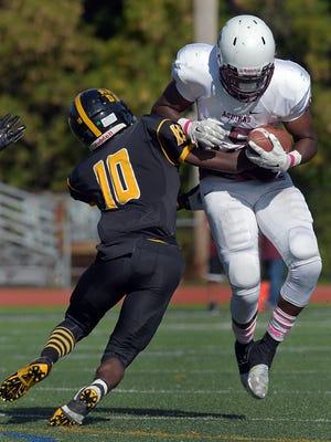 Aquinas' Jamir Jones, right, tries to break the tackle of McQuaid's Atiba McLaren during a regular season game played at McQuaid Jesuit High School on Saturday, October 10, 2015.