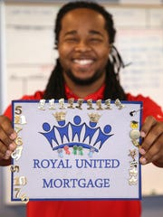 Arias Brown holds up his recognition board, which collects pins for workplace merit, at Royal United Mortgage in Indianapolis. Brown is an assistant vice president of lending.