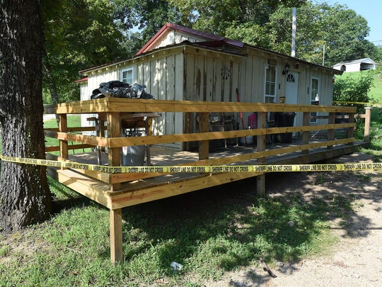 Crime scene tape surrounds the home that was shared by Terry Mills and Sandra Douglas on CR 1428 near Pigeon Creek.