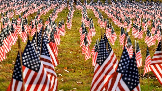 U.S. flags are placed in memory of the men and women who lost their lives in the wars in Afghanistan and Iraq at the campus of Marywood University in Scranton, Pa., on Monday, Nov. 9, 2015.