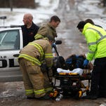 Firefighters and medical personnel tend to an injured Springfield police officer after his car was struck by another in north Springfield on Tuesday afternoon. The driver of the other vehicle fled the scene, and police are looking for white Mercury Mountaineer or Ford Explorer with rear end damage.