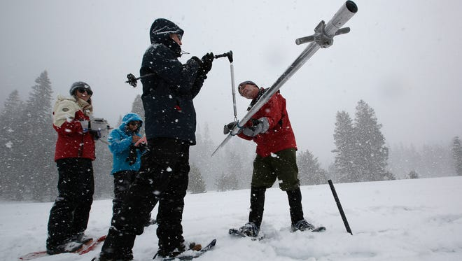 Frank Gehrke, right, chief of the California Cooperative Snow Surveys Program for the Department of Water Resources, places the snow survey tube on a scale held by Nic Enstice, of the Sierra Nevada Conservancy while conducting a manual snow survey at Phillips Station in March 2017.