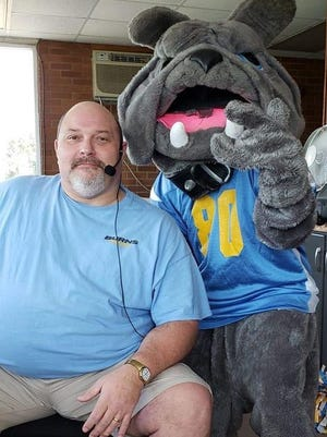 Longtime Burns football public address announcer Tony Beaver poses with the school mascot.