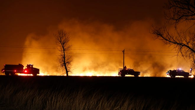 FILE - In this March 6, 2017 file photo, firefighters from across Kansas and Oklahoma battle a  wildfire near Protection, Kan. The La Nina climate phenomenon in the south Pacific Ocean is contributing to weather conditions that are expected to be warm and dry with low humidity, leading to fears of a sharp increase in winter wildfires from the mid-South through the Great Plains.