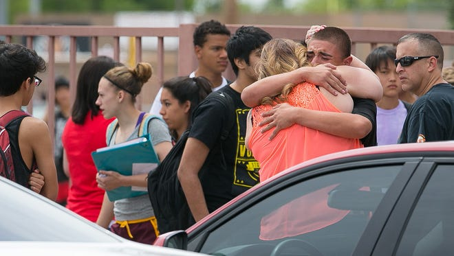 Joanne Arenas hugs her son Aaron after students were let out after an on-campus suicide at Corona del Sol High in Tempe on Tuesday, May 12, 2015.