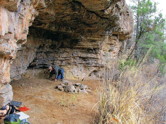 Cody Browning digs a small test pit with a trowel in the rock shelter.