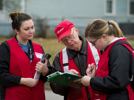 Red Cross volunteer Ron Dame, center, and University of Southern Indiana students Hannah Slauter, left, and Hannah Walker fill out a paperwork as part of the Home Fire Campaign Monday morning. The Red Cross, volunteers, and Mount Vernon firefighters were taking part in MLK Day of Service by installing, testing and replacing batteries for smoke alarms.