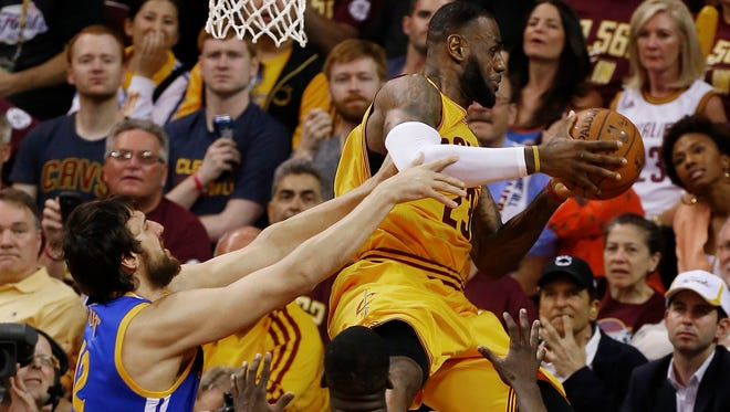 Cleveland Cavaliers forward LeBron James (23) is hit by Golden State Warriors center Andrew Bogut (12) during the first half of Game 4 of basketball's NBA Finals.