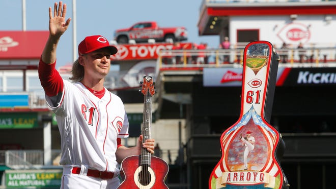 Cincinnati Reds starting pitcher Bronson Arroyo waves to the crowd after receiving a custom made guitar from the Reds during a tribute honoring his career before a game with the Boston Red Sox at Great American Ball Park.