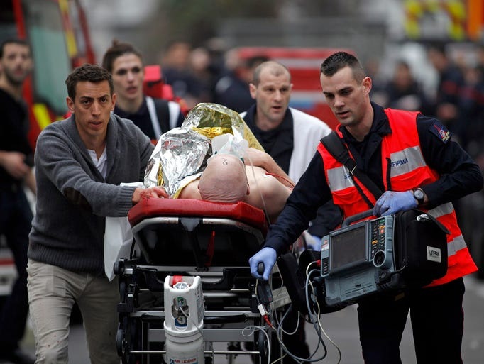 An injured person is evacuated outside the French satirical