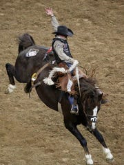 Cody DeMoss competes in the saddle bronc riding event
