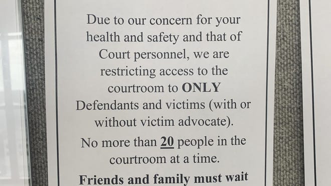 A sign is posted outside of Circuit Judge Caroline Shepherd's courtroom on Wednesday, March 18, 2020, warns those attempting to go inside that only defendants and victims are allowed inside her courtroom and no more than 20 people shall be inside at once due to concern of the spread of coronavirus.